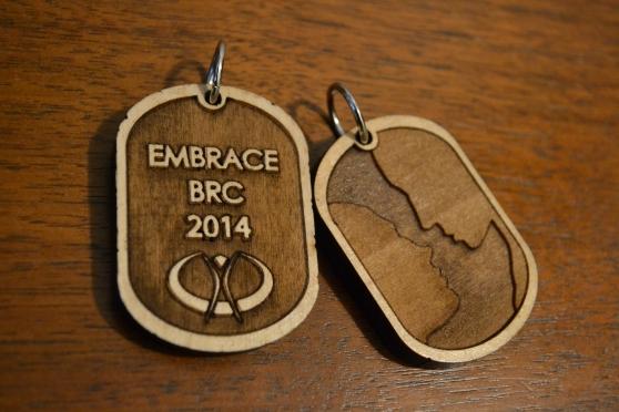 "Laser-cut double-sided Maple Pendants ""Embrace BRC 2014"" Designed by Embrace team member Aleksander Stirajs aka The Fish $20 each"